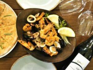Piatto di frutti di mare al sugo di vino bianco con focaccia